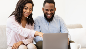 Couple on computer smiling and pointing at screen